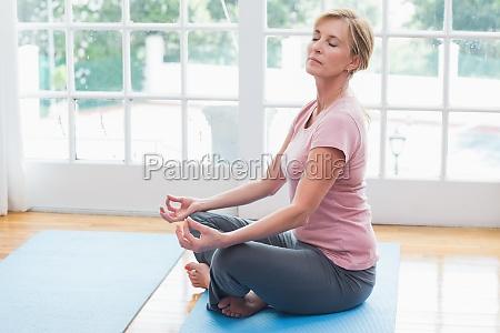aeltere frau die yoga auf fitness