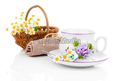 tasse mit kamillenblueten und teebeutel