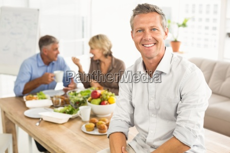 smiling casual businessman sitting on table