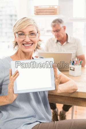 smiling businesswoman showing her tablet