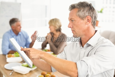 casual businessman using tablet at lunch