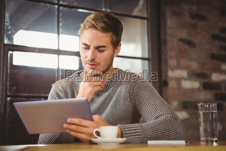 stattlicher mann der sich auf tablet