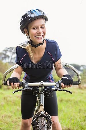 laechelnde athletische blondine mit mountainbike