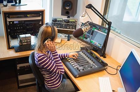 weiblicher radio host der soundmixer bedient