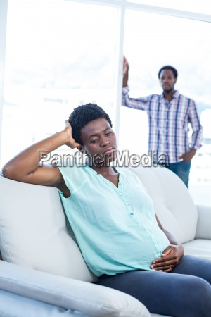 depressed pregnant woman sitting on sofa