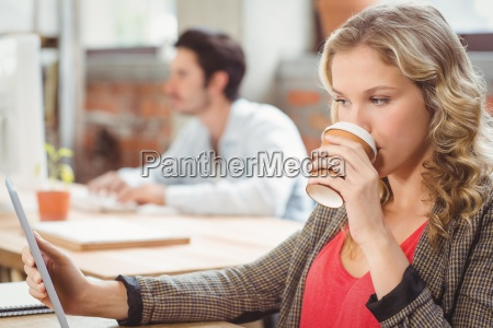 woman drinking coffee while looking at