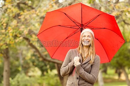 smiling young woman under umbrella