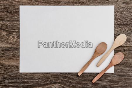 hoelzerne loeffel auf weissem papier und