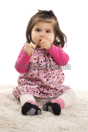 toddler in dress eating a biscuit