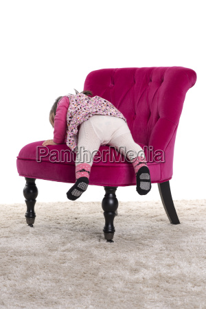 yearling child climbs on a chair