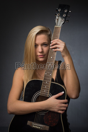 young blond woman holding a guitar