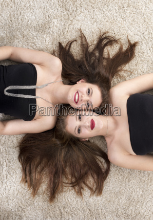 2 girlfriends lying together head to