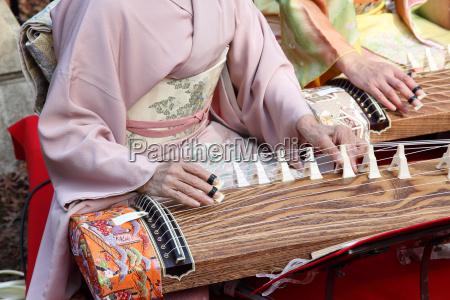 japanische frau die das traditionelle musikinstrument