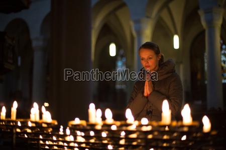 junge frau in einer kirche beten