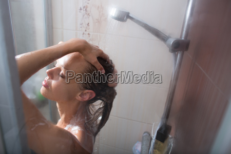 young woman washing her hair with