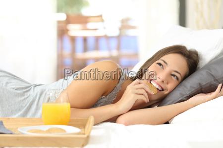 happy girl eating dietetic cookies at