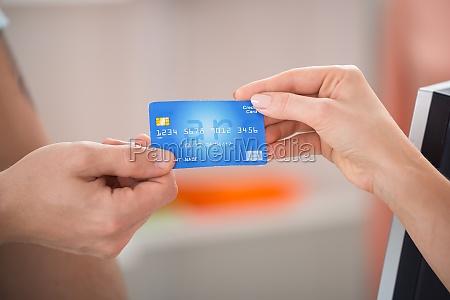 salesman taking credit card from customer
