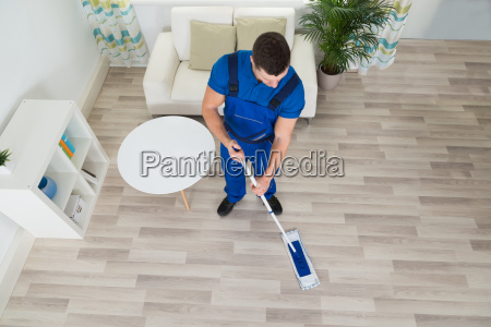 janitor cleaning hardwood floor with mop