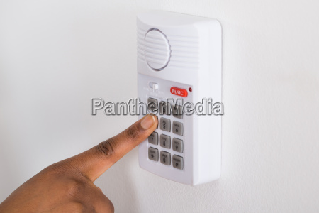 persons hand pressing button on security
