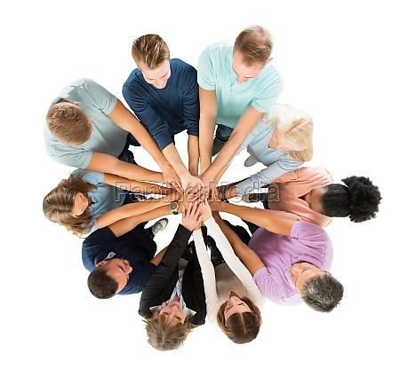 kreative geschaeftsleute stapeln haende in huddle