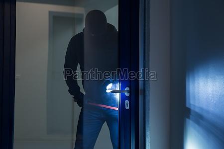 burglar utilizzando crowbar per aprire porta