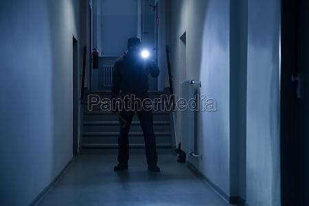 einbrecher mit taschenlampe und crowbar im