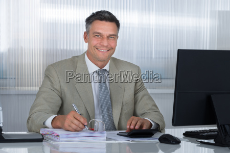 confident accountant using calculator while writing