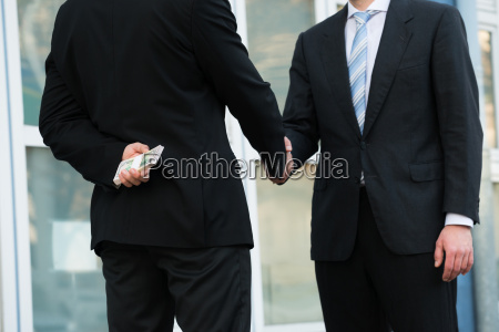 businessman holding dollars while shaking hands