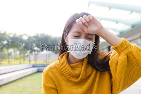frau traegt die gesichtsmaske und kopfschmerzen