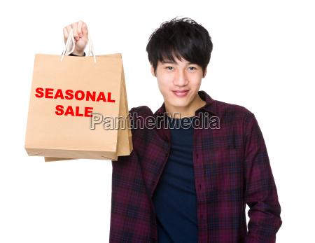 happy asian man shopper holding shopping