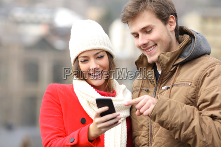 couple consulting a smart phone in