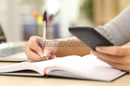 woman hand writing in agenda consulting