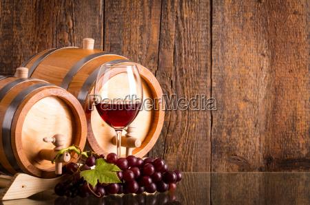 glas rotwein mit zwei faessern und