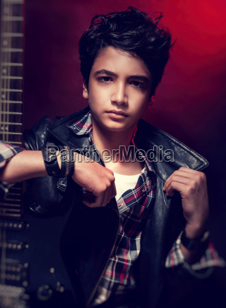 teen guy posing with guitar