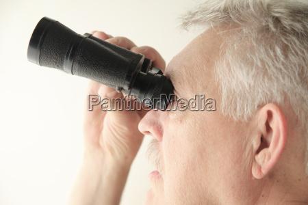man with binoculars looks up