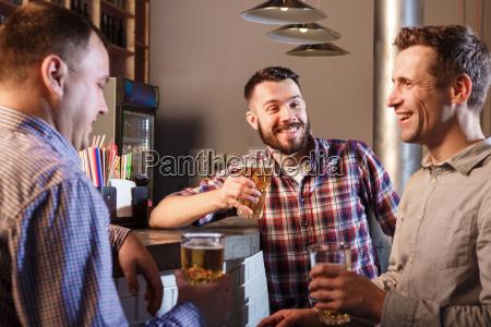 glueckliche freunde die bier trinken am