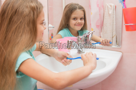 the girl washes a toothbrush under