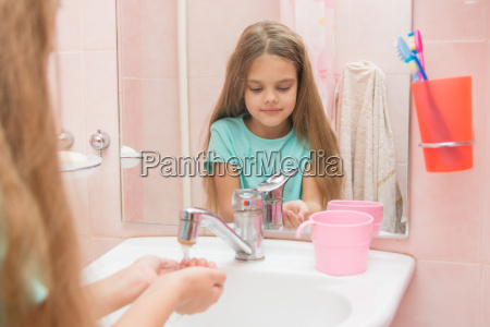 girl pours her hands tap water