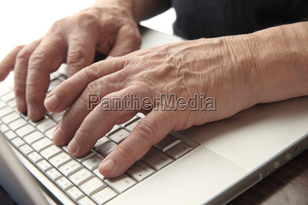 older man types on his laptop