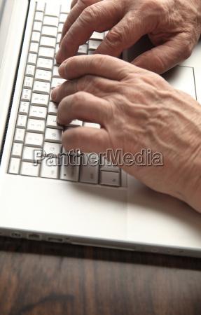 older man works on laptop