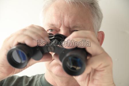 older man holds binoculars