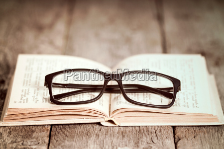reading glasses on the old book