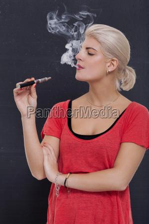 junge attraktive blonde frau raucht eine