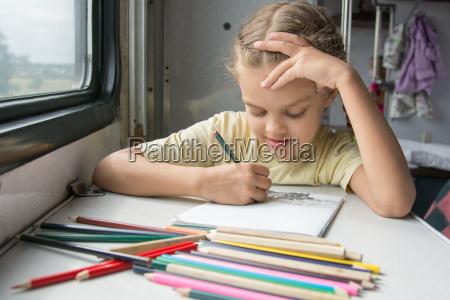 six year girl joyfully draws pencils