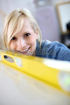 closeup of blond woman using level