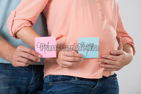 expecting couple holding paper with girl
