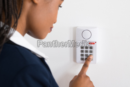businesswoman pressing button on security system