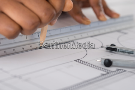 persons hand drawing blue print