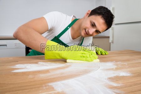 cleaner cleaning dust on wooden table