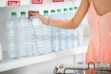 frau kauft eine flasche mineralwasser im